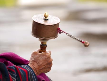 Een oudere Boeddhistische vrouwen spinnen haar gebedsmolen voor goede mantra