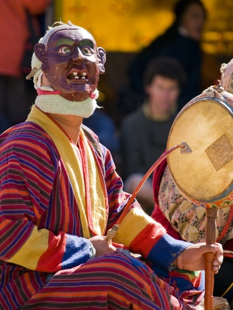 Masked man making music during a tsechus (Bhutanese festival) in Bumthang, Bhutan Stock Photo