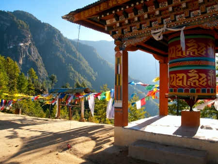 prayer: View of the Taktshang monastery in Paro (Bhutan) with prayer flags and a prayer wheel in the front