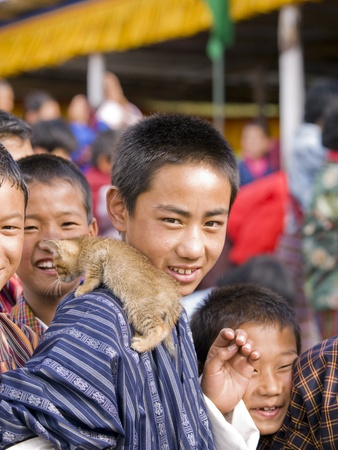 THIMPU, BHUTAN -  OCTOBER 20, 2010: Unidentified kids with a kitten at a tsechu on Oct. 20, 2010 near Thimpu. Tsechu are annual religious Bhutanese festivals usually around the time of October. Stock Photo - 12533453