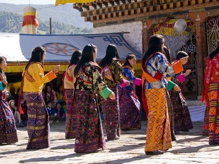 JAKAR, BHUTAN - OCTOBER 24, 2010: Women wearing traditional kira dresses dancing at the Jakar tsechu on Oct. 24, 2010 in Jakar. Tsechu are annual religious Bhutanese festivals, usually around October