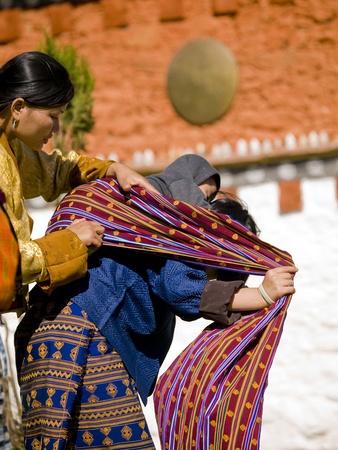 Jakar, Bhutan-24 oktober 2010: Meisje helpt een andere vrouw te binden haar baby op haar rug op de Jakar Tsechu op 24 oktober 2010 in Jakar. Tsechu zijn religieuze Bhutanese festivals meestal rond oktober