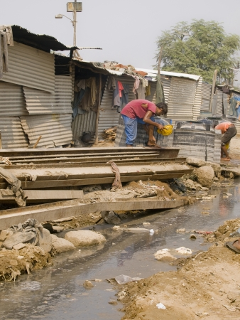 poverty india: JAIPUR, INDIA - NOVEMBER 2, 2010  Poor man in the slums in India trying to get clean drinking water on November 2nd, 2010 near Jaipur  Poverty is a real big problem everywhere in India