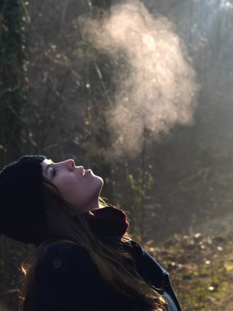 breath: Beautiful girl breathing warm air during a cold autumn morning