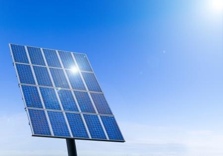 青い空を背景に、太陽電池パネルで輝く太陽