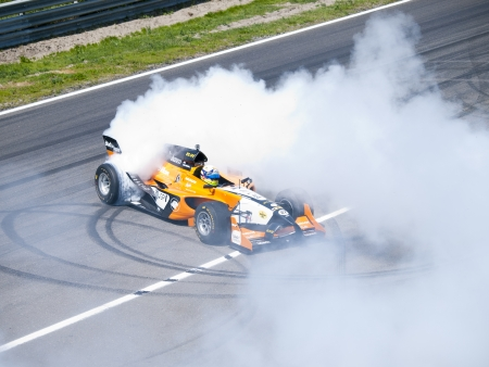 wheelspin: ZANDVOORT, NETHERLANDS - JULY 7: Tom Coronel burns some rubber in an AutoGP Formula car with a V8 Zytek motor during a demonstration at the RTL GP Masters in Zandvoort on July 7, 2013 in Zandvoort, Holland.