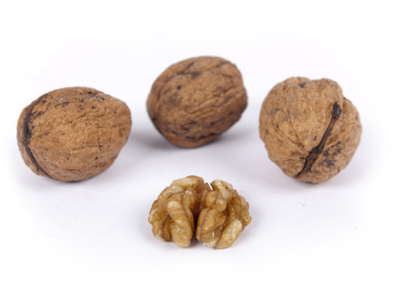 nutshells: Peeled walnut with closed nutshells behind it Stock Photo