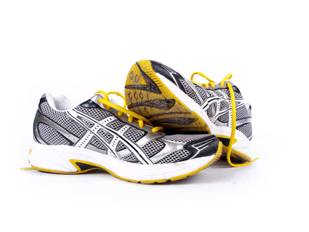 running shoes: Used dirty pair of running shoes over a white
