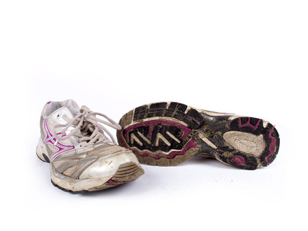 old shoes: Very old dirty pair of running shoes over a white background