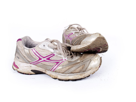 Very old dirty pair of running shoes over a white
