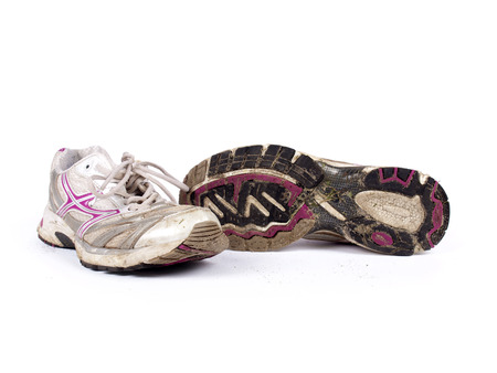 Very old dirty pair of running shoes over a white background photo