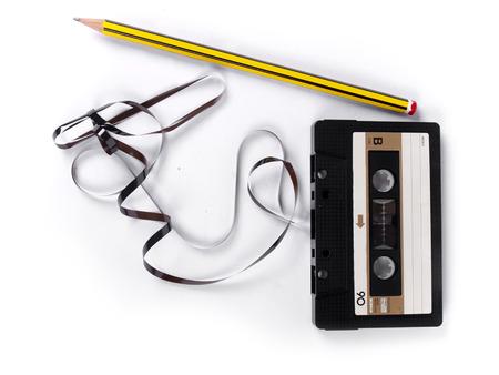 retro cassette met losse band en een potlood om terug te spoelen op een witte achtergrond