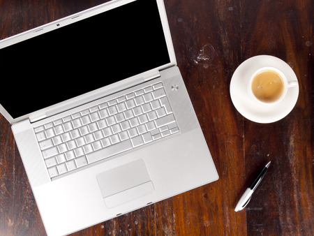 Modern laptop with a cup of coffee next to it photo