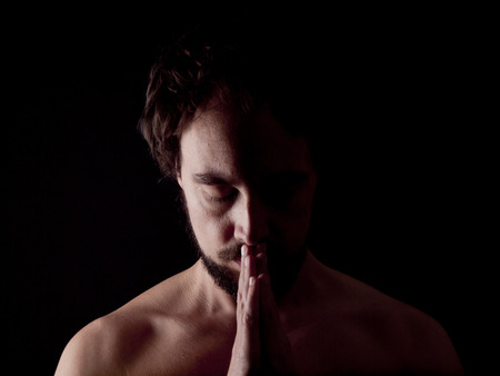 confessing: Low key image of a bearded man praying
