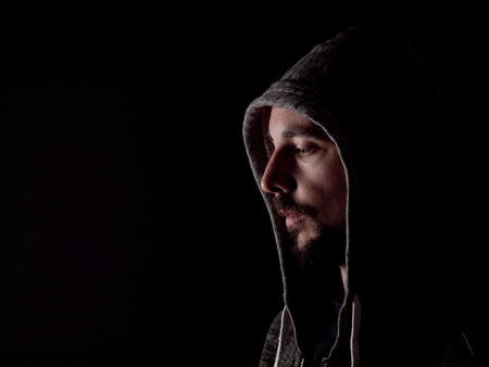 hoody: Low key image of a bearded man with a hoody