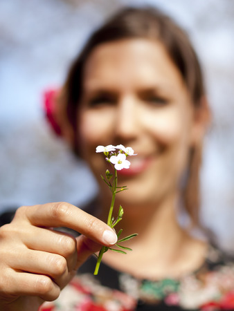 Beautiful girl handing over a cuckoo flower during a picnic in the spring photo
