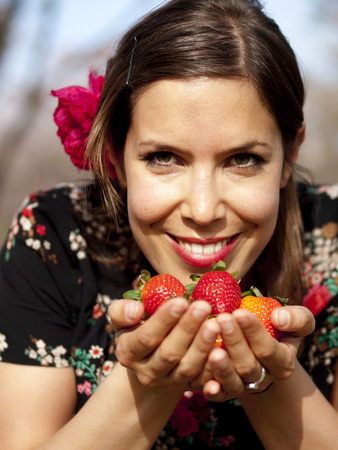 Beautiful girl smelling fresh strawberries in her hand during a picnic in the spring photo