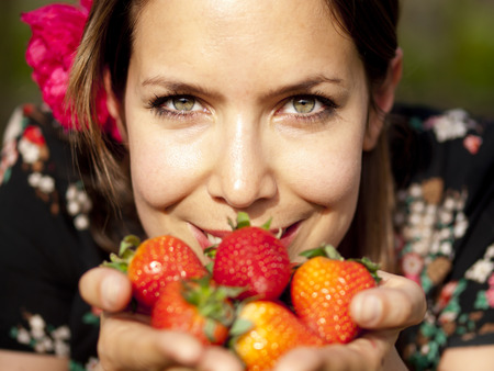Beautiful girl smelling fresh strawberries in her hand during a picnic in the spring