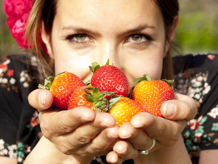 Beautiful girl smelling strawberries during a picnic in the spring photo