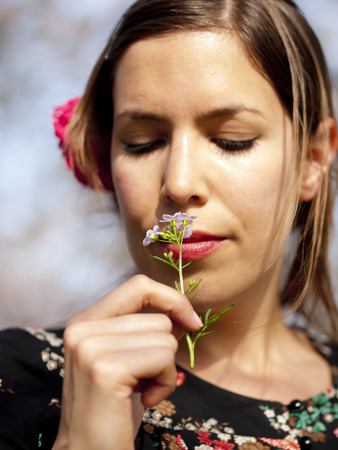 Beautiful girl smelling a cuckoo flower during a picnic in the spring photo