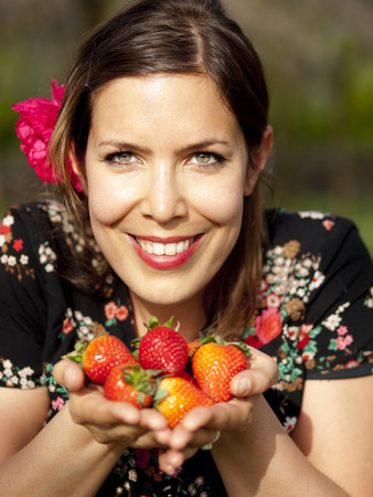 Beautiful girl showing strawberries during a picnic in the spring photo