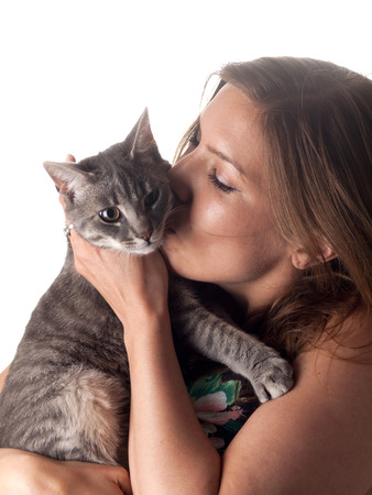 Smiling beautiful brunette kissing and petting her cute grey 7 month old cat Stock Photo