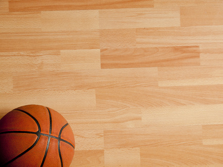 An official orange ball on a hardwood basketball court Stock Photo