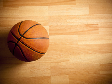 basketball team: An official orange ball on a hardwood basketball court Stock Photo