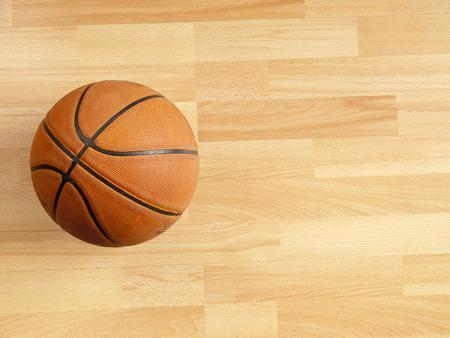 Een officieel oranje bal op een hardhouten basketbalveld Stockfoto