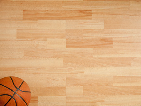 hardwood: An official orange ball on a hardwood basketball court Stock Photo
