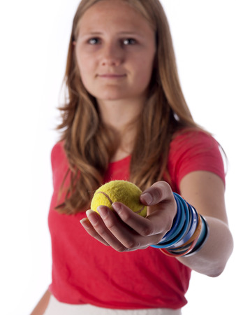 Young teenage girl holding a tennis ball in front of her over a white background photo