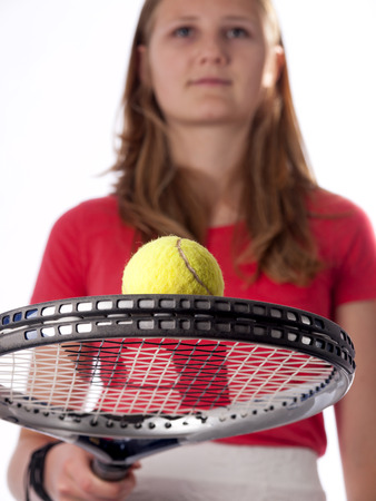 Young teenage girl holding a tennis racket and ball over a white background photo