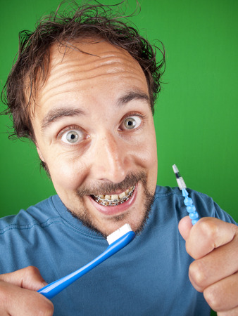 dentalcare: Thirty year old man with braces and a toothbrush over a green background