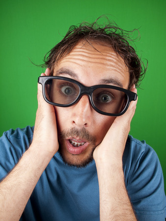 Thirty year old man with 3d glasses watching a movie over a green background photo