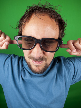 Thirty year old man with 3d glasses is too afraid to watch the movie over a green background photo