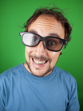 Thirty year old man with 3d glasses is watching a funny movie over a green background photo