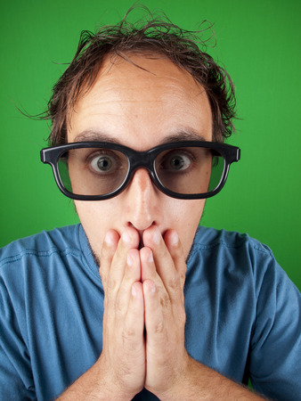 Thirty year old man with 3d glasses in shock watching a movie over a green background photo