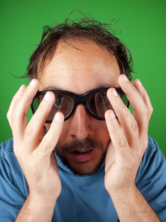 Thirty year old man with 3d glasses is too afraid to watch the scary movie over a green background photo