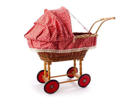 An old vintage childrens doll stroller over a white background photo