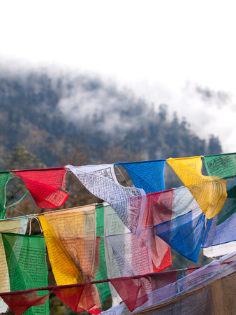 Colorful prayer flags over the misty himalayas at the Dochula Pass between Punakha and Thimpu in Bhutan photo