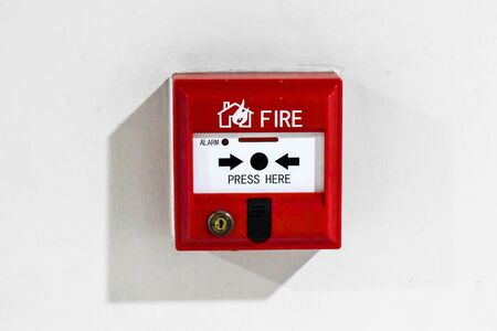 A red Switch fire alarm box with white background at a condominium in Bangkok Thailand Stock Photo