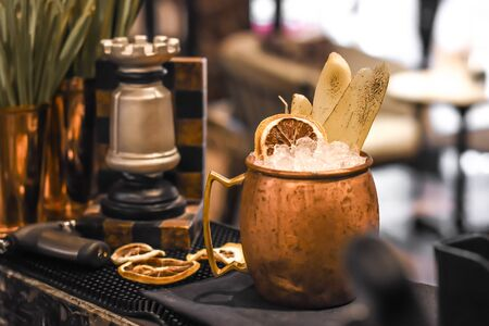 Signature cocktail decorated with burn giner and  Dehydrated lemon wheel in mosco mule mug Stockfoto