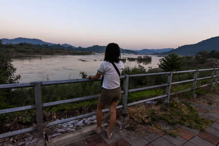 Back side of a asian lady looked at natural landscape view of Mae Khong river at Sang khom idstrict ,Nong Khai province Thailand Banco de Imagens