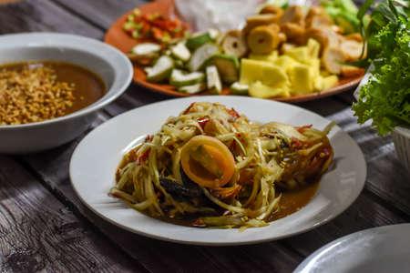 Spicy thai green papaya salad or thai name Som Tum (a famous local thai street food) with Nam Neung (Vietnamese Meatball Wraps) background