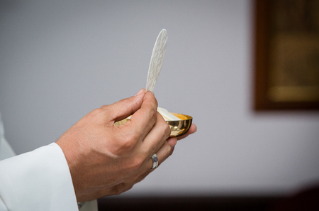 Closeup of priest with communion in the hand. Religious ceremony. Holy communion on a catholic mass. Concept: Free from sins. Stock Photo