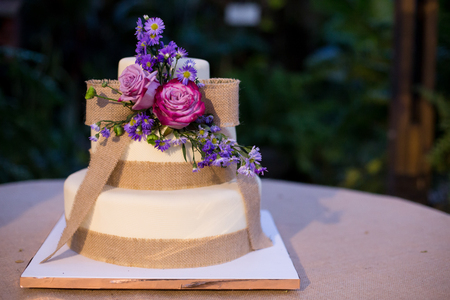 Wedding, Birthday Cake with flowers at the reception. Social event concept. Cake for a birthday celebration or a wedding reception.