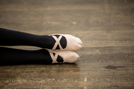 ballet dancer feet with black stockings and slippers on a wooden rustic floor. Copy space. Ballet performance. Isolated ballet shoes.