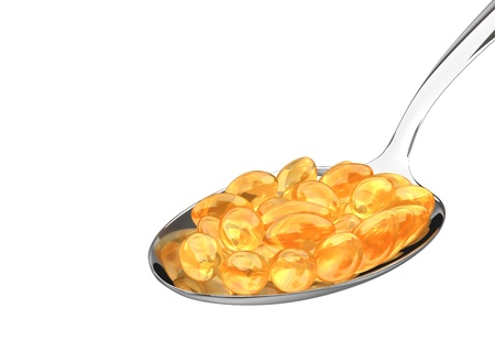 Vitamin pills on spoon isolated on white background. Stock Photo - 8677452