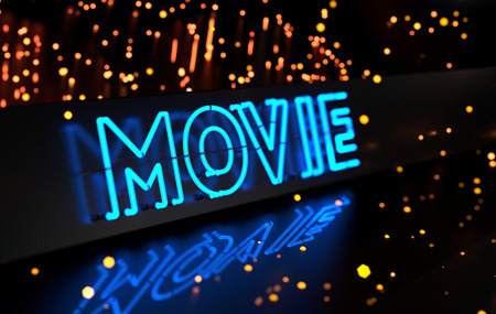 entertainment event: Neon Movie Sign on Dark Blurred Background Stock Photo