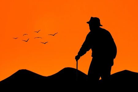 Oude man lopen bij zonsondergang met bergen en vogels op de achtergrond